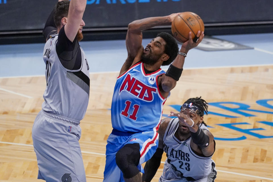 Brooklyn Nets guard Kyrie Irving (11) goes to the basket against Portland Trail Blazers center Jusuf Nurkic and forward Robert Covington (23) during the first half of an NBA basketball game, Friday, April 30, 2021, in New York. (AP Photo/Mary Altaffer)