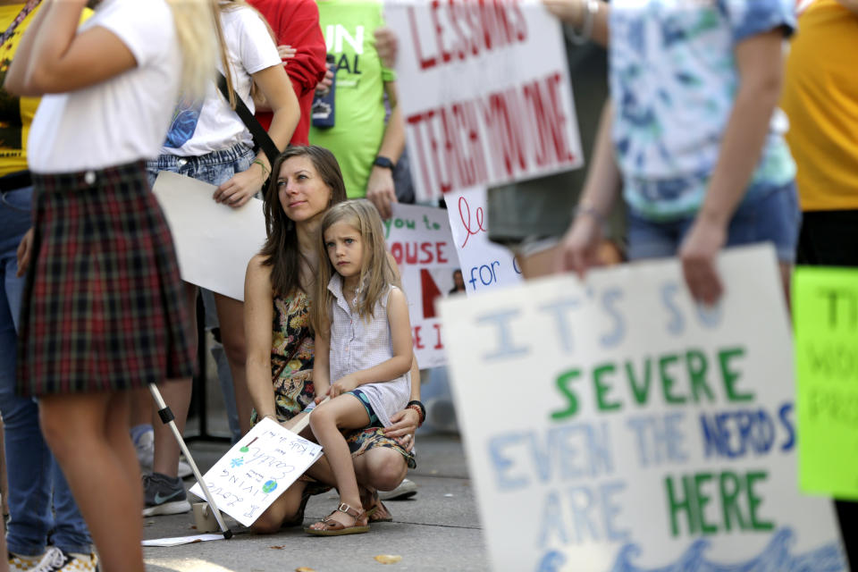 Emily Hill and her daughter Josephine Hill, 6, of Bellevue, Neb.,listen to speakers during a youth climate strike week action in Omaha, Neb., Friday, Sept. 20, 2019.  (Photo: Nati Harnik/AP)