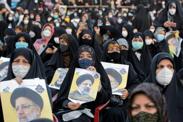 Supporters of Iranian presidential candidate Ebrahim Raisi hold up his poster during an election campaign rally on June 6, where Raisi has cast himself as the anti-corruption champion of the poor