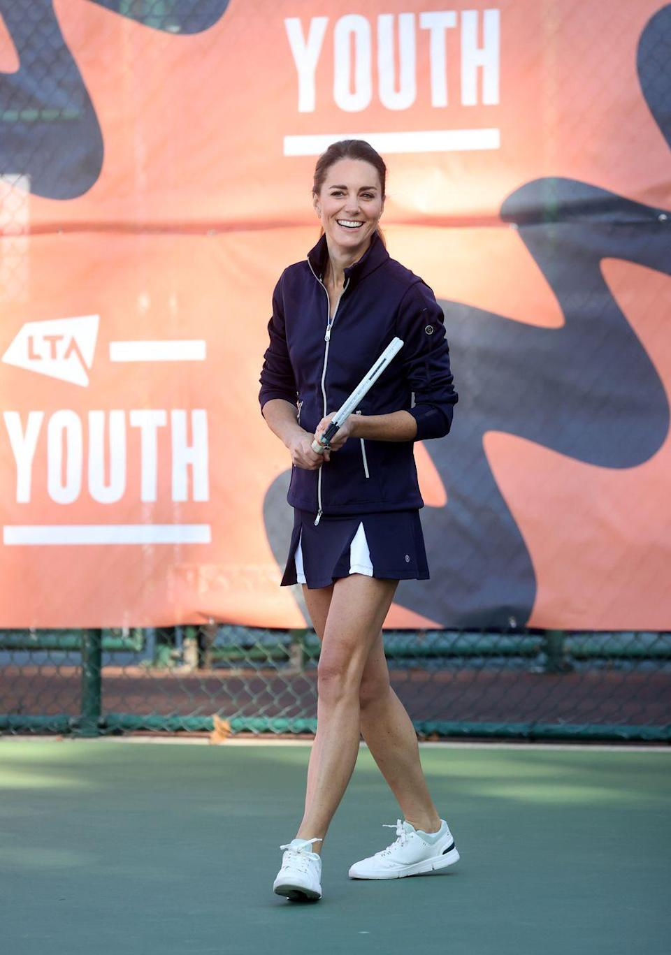 """<p>In case there was any doubt about the stylishness of the <a href=""""https://www.townandcountrymag.com/style/g37374577/best-tennis-outfits/"""" rel=""""nofollow noopener"""" target=""""_blank"""" data-ylk=""""slk:tennis fashion trend"""" class=""""link rapid-noclick-resp"""">tennis fashion trend</a>, Kate donned a perfectly put-together navy blue tennis skirt with contrasting white panels, a navy and white jacket, and <a href=""""https://www.townandcountrymag.com/style/g28073171/best-white-sneakers-for-women/"""" rel=""""nofollow noopener"""" target=""""_blank"""" data-ylk=""""slk:white sneakers"""" class=""""link rapid-noclick-resp"""">white sneakers</a> for a <a href=""""https://www.townandcountrymag.com/society/tradition/a37721234/kate-middleton-plays-tennis-with-us-open-champion-emma-raducanu-photos/"""" rel=""""nofollow noopener"""" target=""""_blank"""" data-ylk=""""slk:doubles match with US Open Champion Emma Raducanu"""" class=""""link rapid-noclick-resp"""">doubles match with US Open Champion Emma Raducanu</a>. </p>"""