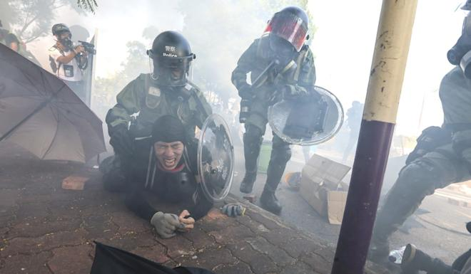 Riot police fire tear gas and arrest protesters outside Chinese University in Sha Tin early on Monday. Photo: Felix Wong