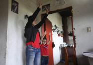 Marlene Beltran, 14, left, and her brother Felipe Beltran, 5, exercise during a gym class broadcast through Bacata Stereo radio station during the lockdown to prevent the spread of the new coronavirus in Funza, Colombia, Wednesday, May 13, 2020. While schools are closed during the lockdown to curb the spread of COVID-19, teachers in the municipality of Funza broadcast their lessons through the radio station because many students do not have access to the Internet. (AP Photo/Fernando Vergara)