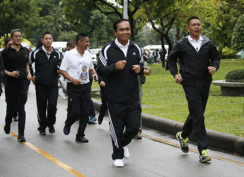In this Oct. 5, 2018, photo, Thai Prime Minister Prayuth Chan-ocha, center, jogs in Lumpini park in central Bangkok, Thailand. Prayuth became prime minister in a very Thai way: He led a military coup. Now after five years of running Thailand with absolute power, he's seeking to hold on to the top job through the ballot box. (AP Photo/Sakchai Lalit)
