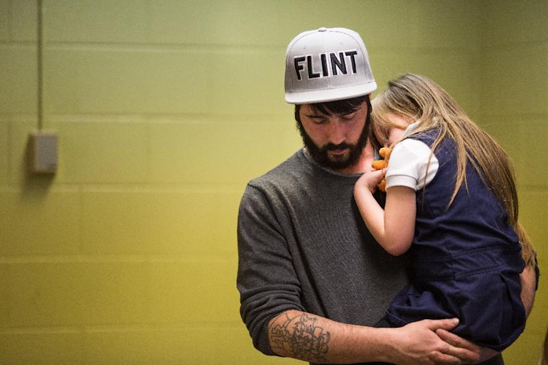 Matt Hopper comforts Nyla Hopper, age 5 of Flint, after she has her blood drawn to be tested for lead at Eisenhower Elementary School in Flint, Michigan (AFP Photo/Brett Carlsen)
