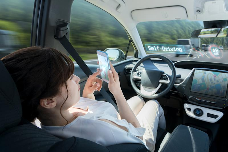 Woman on a smart phone in a driverless vehicle.