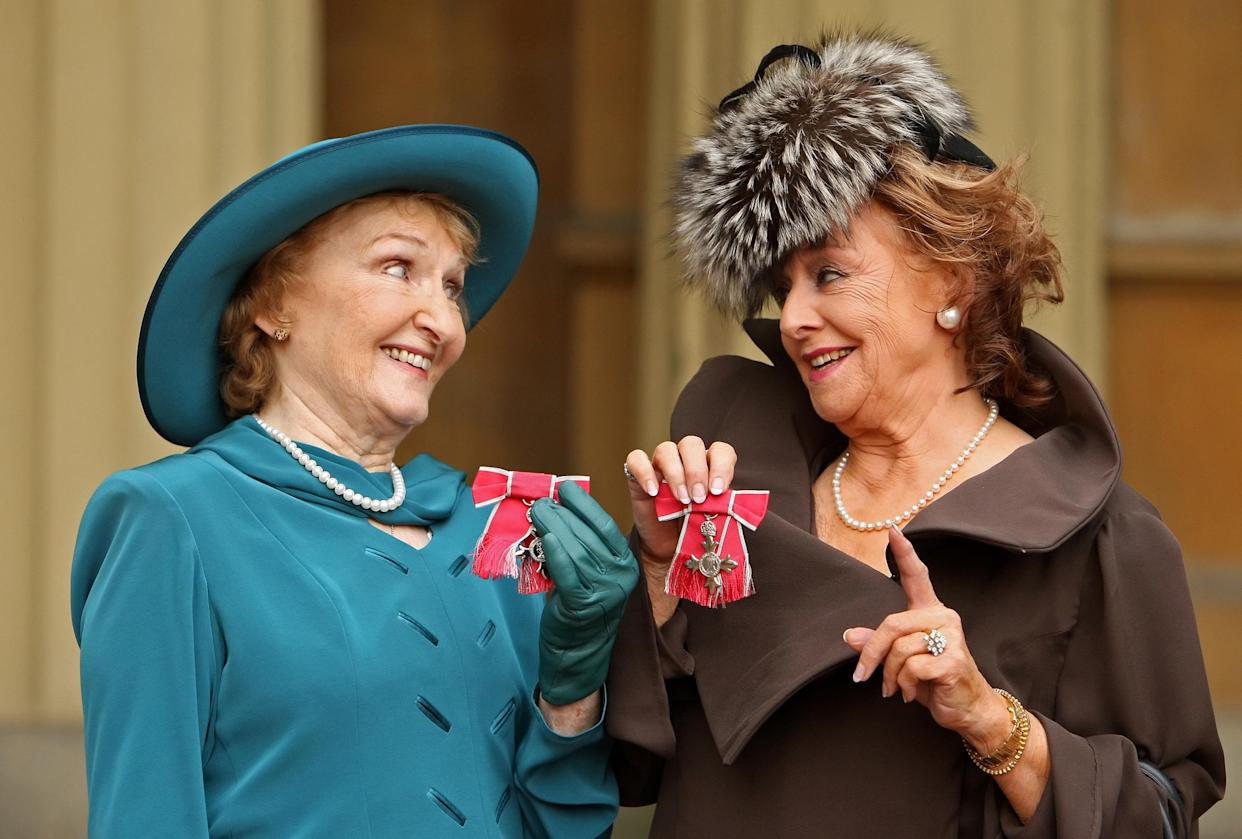 Eileen Derbyshire (L) and Barbara Knox, actresses in British television programme 'Coronation Street', pose for photographers with their MBEs (Member of the British Empire), after they were awarded them by Britain's Queen Elizabeth II, during an Investiture ceremony at Buckingham Palace in London on November 3, 2010.         AFP PHOTO / Dominic Lipinski / Pool (Photo credit should read Dominic Lipinski/AFP via Getty Images)