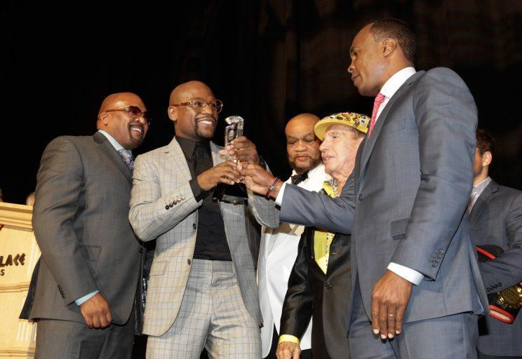 Hall of Fame boxer Sugar Ray Leonard (R) presents an award to Floyd Mayweather (second from left) at the Nevada Boxing Hall of Fame ceremony in 2015. (Getty Images)