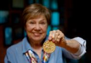 Legendary Soviet gymnast Larisa Latynina shows her Olympic gold medal got in the Olympic Games in Tokyo in 1964, in her home in village Kalyanino