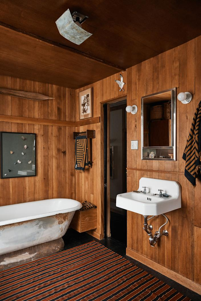 "<div class=""caption""> Aujla and Bode's wood-clad bathroom features a vintage soaking tub that looks out over Lower Manhattan. </div>"