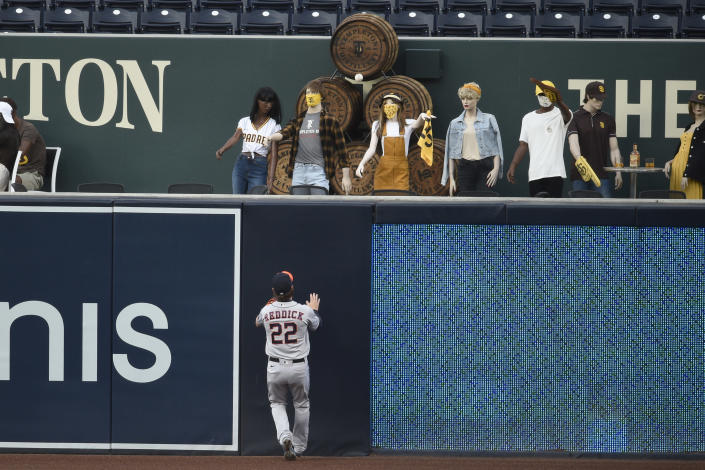 Houston Astros right fielder Josh Reddick looks into the stands filled with mannequins, after a solo home run by San Diego Padres' Trent Grisham during the first inning of a baseball game in San Diego, Saturday, Aug. 22, 2020. (AP Photo/Kelvin Kuo)