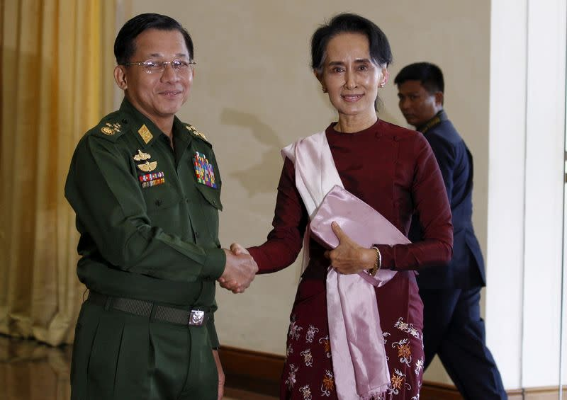 FILE PHOTO: Senior General Min Aung Hlaing, Myanmar's commander-in-chief, shakes hands with National League for Democracy (NLD) party leader Aung San Suu Kyi before their meeting in Hlaing's office at Naypyitaw