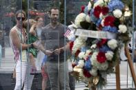 Retired Army Capt. Stephen Hunnewell stands with his wife Jessica and daughter Elizabeth behind a wreath in memory of Marine Sgt. Johanny Rosario Pichardo from Lawrence, Mass., following a ceremony at the Massachusetts Fallen Heroes Memorial, Saturday, Aug. 28, 2021, in Boston.The ceremony was held to honor the U.S. service members killed in a suicide bombing at the airport in Kabul, Afghanistan, including Sgt. Rosario Pichardo. (AP Photo/Michael Dwyer)