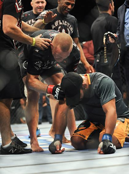 GSP tried to console Johny Hendricks after the decision was read. (USA Today)