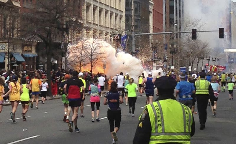 FILE PHOTO: File photo of runners continue to run towards the finish line as an explosion erupts at the finish line of the Boston Marathon