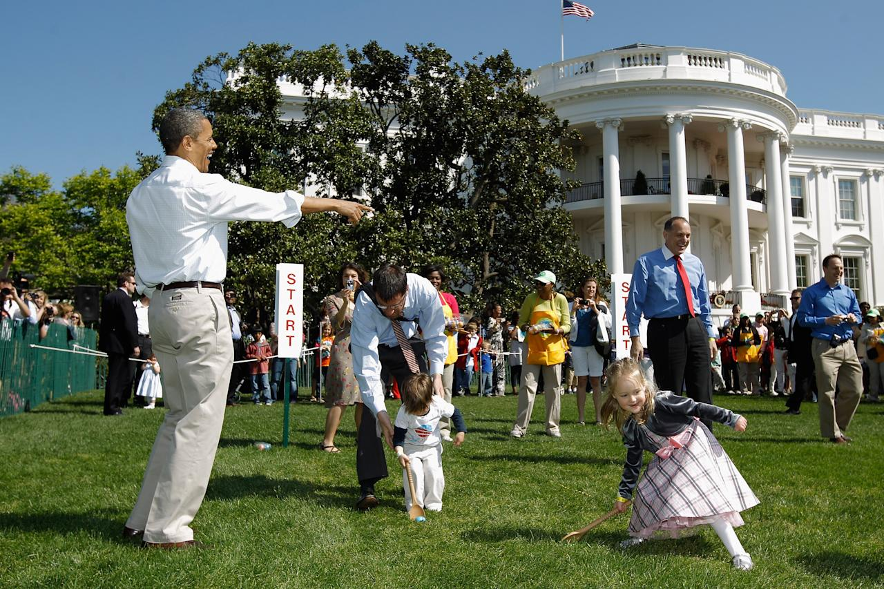 U.S. President Barack Obama (L) watches participants roll eggs during the White House Easter Egg Roll on the South Lawn of the White House on April 9, 2012 in Washington, DC. Thousands of people people are expected to attend the 134-year-old tradition of rolling colored eggs down the White House lawn that was started by President Rutherford B. Hayes in 1878.  (Photo by Chip Somodevilla/Getty Images)