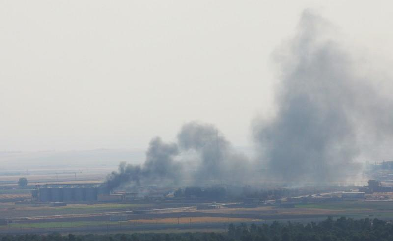 Smoke rises from a building near the Syrian town of Ras al-Ain as seen from the Turkish border town of Ceylanpinar