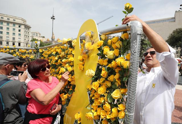 People decorate a fence with yellow roses in support of imprisoned pro-independence leaders during Sant Jordi's day at Catalunya square in Barcelona, Spain April 23, 2018. REUTERS/Albert Gea