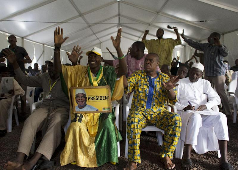 Supporters of Ibrahim Boubacar Keita briefly celebrate as they watch the televised reading of election results, at Keita campaign headquarters in Bamako, Mali, Friday, Aug. 2, 2013. Mali's presidential race will go to a second round on Aug. 11. Keita finished with a strong lead over his next closest rival, Soumaila Cisse, but still well shy of the majority needed to win outright in the first round.(AP Photo/Rebecca Blackwell)