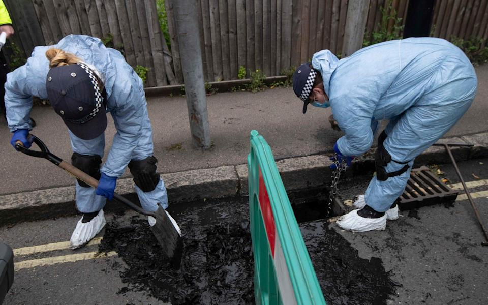 Police forensics officers search for evidence in drains in the street near where Ms Johnson was shot
