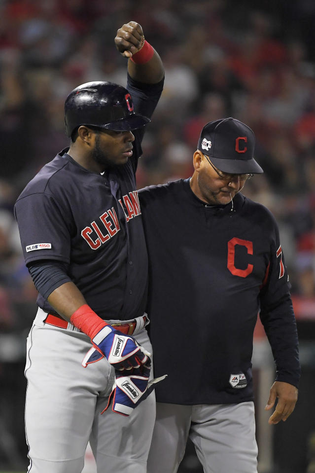 Cleveland Indians' Yasiel Puig, left, is accompanied by manager Terry Francona on the way to first after being hit by a pitch for the second time of the night, during the third inning of the team's baseball game against the Los Angeles Angels on Tuesday, Sept. 10, 2019, in Anaheim, Calif. (AP Photo/Mark J. Terrill)