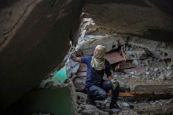 """A firefighter searches for survivors inside a damaged building in Les Cayes on Aug. 15.<span class=""""copyright"""">Joseph Odelyn—AP</span>"""