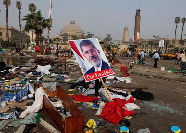 An Egyptian carries a poster of Egypt's ousted President Mohammed Morsi among debris from a protest camp in Nahda Square, Giza, Cairo, Egypt, Thursday, Aug. 15, 2013. Egypt faced a new phase of uncertainty on Thursday after the bloodiest day since its Arab Spring began, with over 300 people reported killed and thousands injured as police smashed two protest camps of supporters of the deposed Islamist president. Wednesday's raids touched off day-long street violence that prompted the military-backed interim leaders to impose a state of emergency and curfew, and drew widespread condemnation from the Muslim world and the West, including the United States. (AP Photo/Amr Nabil)