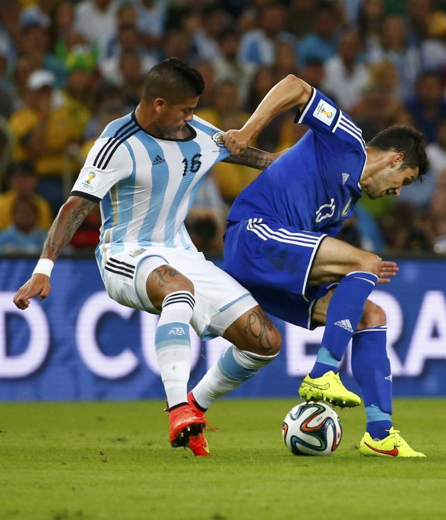 Argentina's Marcos Rojo (R) and Bosnia's Mensur Mujdza fight for the ball during their 2014 World Cup Group F soccer match at the Maracana stadium in Rio de Janeiro June 15, 2014. REUTERS/Michael Dalder (BRAZIL - Tags: SOCCER SPORT WORLD CUP)