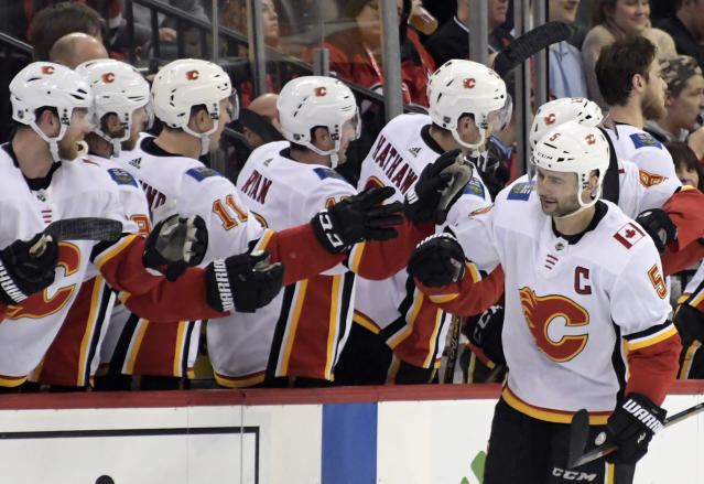 Calgary Flames defenseman Mark Giordano (5) celebrates his goal with teammates during the second period of an NHL hockey game against the New Jersey Devils Wednesday, Feb. 27, 2019, in Newark, N.J. the Flames won 2-1. (AP Photo/Bill Kostroun)