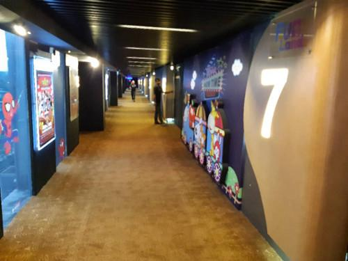 The cinema corridor adorned with posters at Cinehouse, One City Skypark.