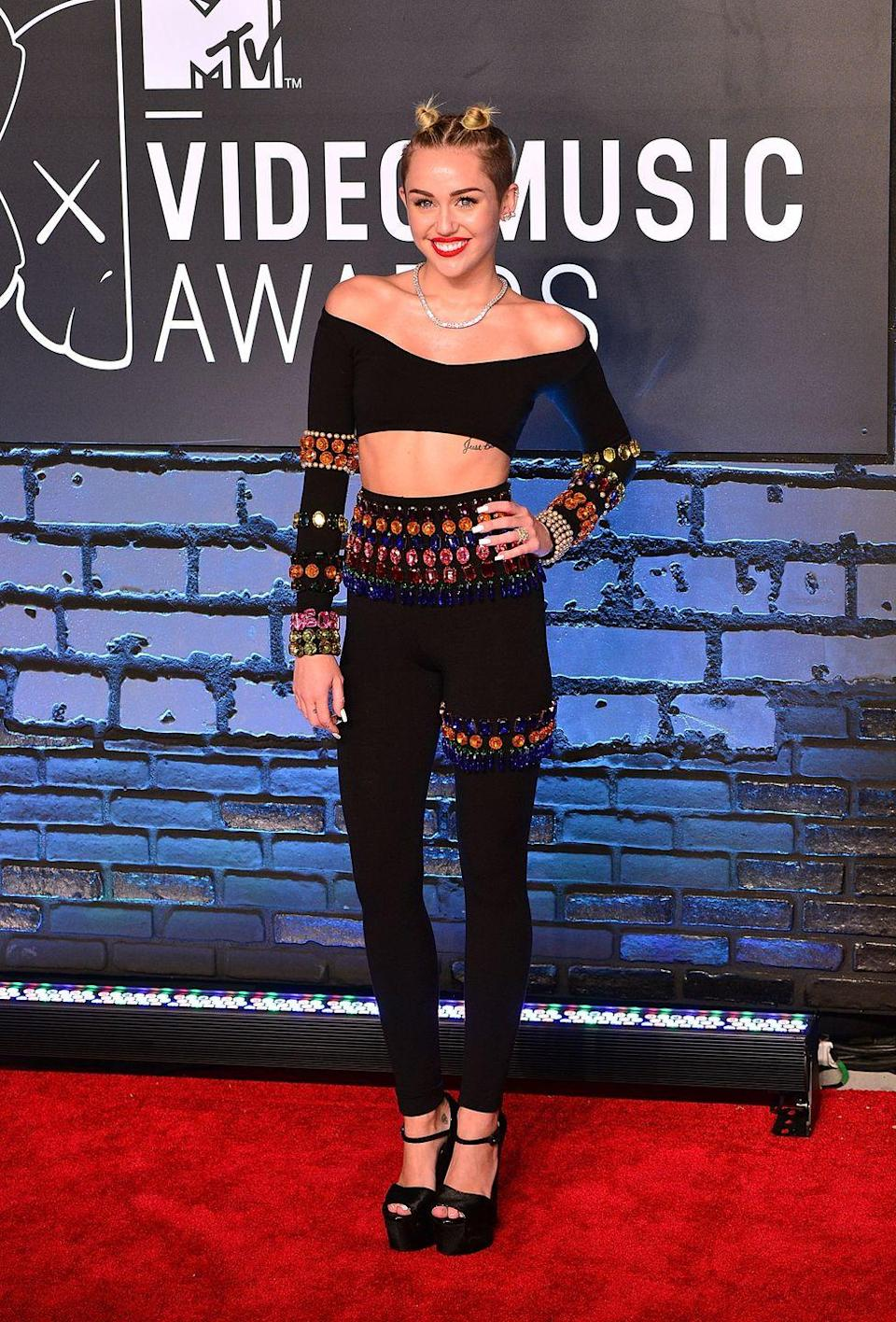 <p>Miley Cyrus's sexy embellished two-piece look—with her mini space buns—signaled a new aesthetic phase for her in 2013.</p>