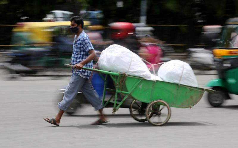 An Indian man pulling hand cart in a busy market area, during an extended lockdown over suspected coronavirus disease (COVID-19) cases in Bangalore, India - Shutterstock