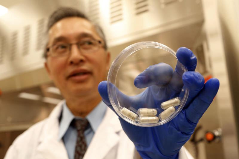 Dr. Thomas Louie, an infectious disease specialist at the University of Calgary, holds a container of stool pills in triple-coated gel capsules in his lab in Calgary, Alberta, Canada on Thursday, Sept. 26, 2013. Half a million Americans get Clostridium difficile, or C-diff, infections each year, and about 14,000 die. A very potent and pricey antibiotic can kill C-diff but also destroys good bacteria that live in the gut, leaving it more susceptible to future infections. Recently, studies have shown that fecal transplants - giving infected people stool from a healthy donor - can restore that balance. (AP Photo/The Canadian Press, Jeff McIntosh)