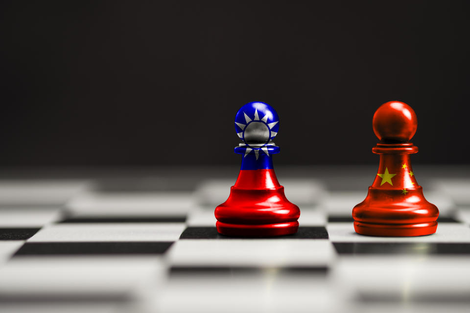 China and Taiwan flag print screen on pawn chess with black background. Now both countries have economic and patriotic conflict.