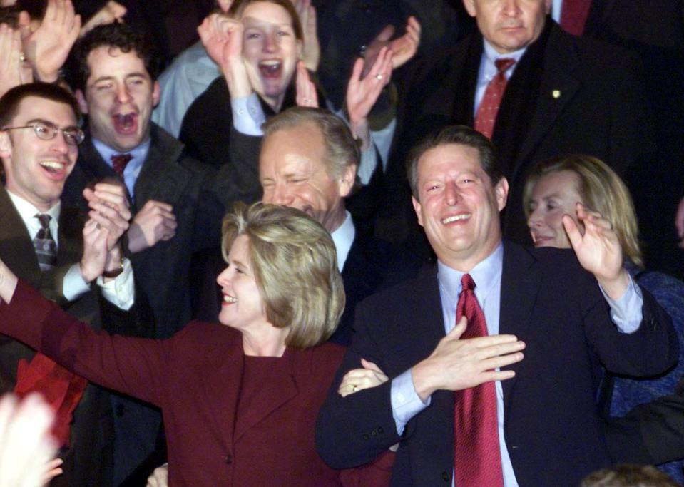 Al and Tipper Gore, arm in arm, stand amid smiling, applauding supporters
