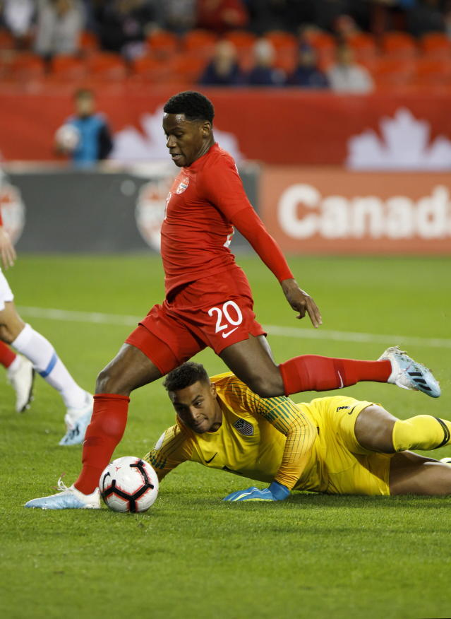 United States goalkeeper Zack Steffen (1) watches through the legs of Canada forward Jonathan David (20) as he lines up a shot on net during the first half of a CONCACAF Nations League soccer match Tuesday, Oct. 15, 2019, in Toronto. (Cole Burston/The Canadian Press via AP
