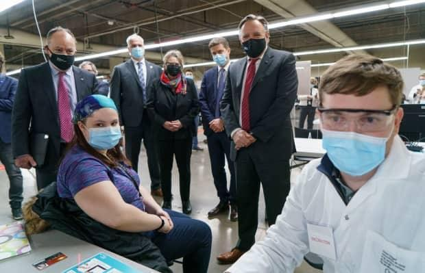 Quebec Premier François Legault and Health Minister Christian Dubé watch a woman register for her COVID-19 vaccine at a clinic in Montreal's Olympic Stadium