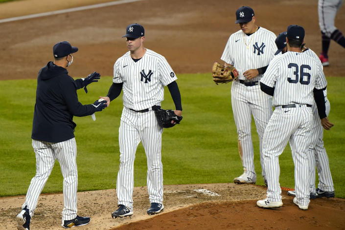 New York Yankees manager Aaron Boone. left, takes the ball from starting pitcher Corey Kluber as infielders stand on the mound during the fifth inning of the team's baseball game against the Atlanta Braves, Wednesday, April 21, 2021, at Yankee Stadium in New York. (AP Photo/Kathy Willens)