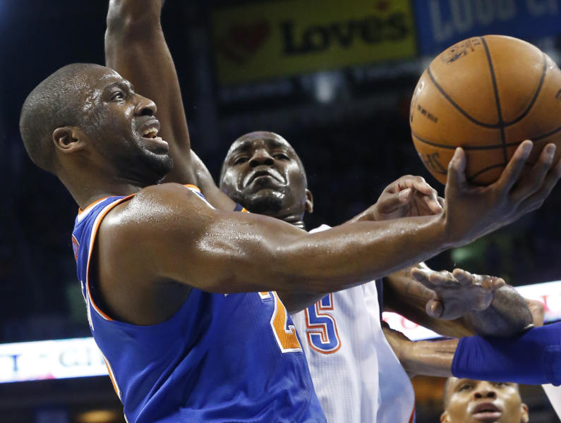 New York Knicks guard Raymond Felton (2) shoots in front of Oklahoma City Thunder center Kendrick Perkins (5) in the first quarter of an NBA basketball game in Oklahoma City, Sunday, April 7, 2013. (AP Photo/Sue Ogrocki)
