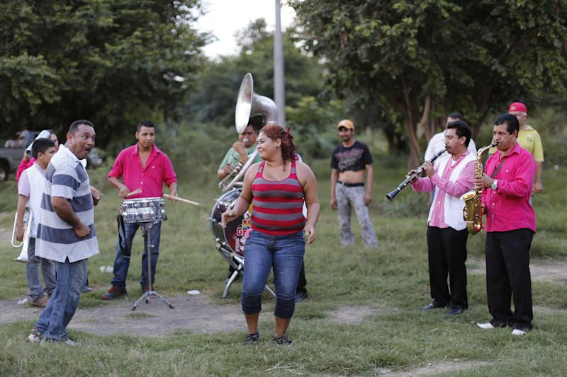 """In this Nov. 5, 2013 photo, villagers dance as tensions ease after they gathered to block the road in response to army soldiers allegedly confiscating a few weapons from the community's self-defense group in the town of in Las Colonias, in the state of Michoacan, Mexico. The group says that soldiers confiscated a few of their weapons and that their leaders were negotiating with the army to get them back. Months after locals formed self-defense groups, they say they are free of the Knights Templar cartel in some municipalities of the Tierra Caliente, or """"Hot Land."""" (AP Photo/Dario Lopez-Mills)"""
