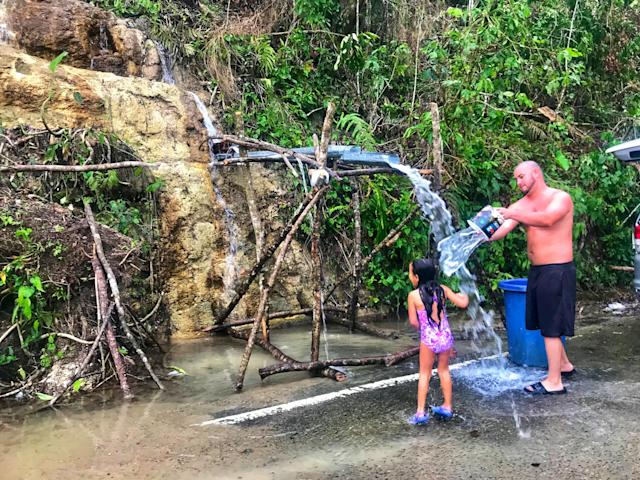 <p>A young girl and her father rinse off in naturally flowing water from the side of a mountain in Ciales, Puerto Rico on Oct. 11, 2017. (Photo: Caitlin DIckson/Yahoo News) </p>