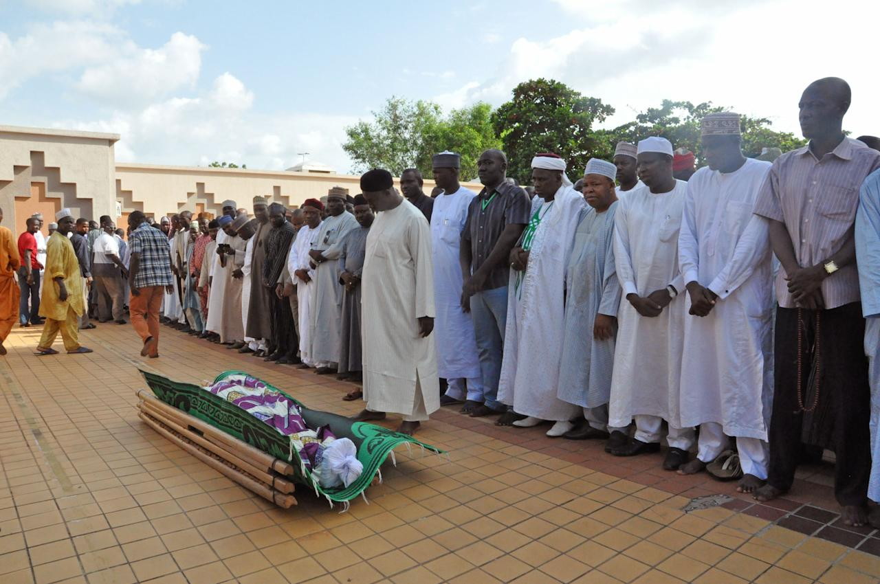 People stand over the remains blast victim Suleiman Bisalla , during his funeral, after the explosion in Abuja, Nigeria, Thursday, June 26, 2014. The National Hospital spokesman says a victim wounded in the bomb blast at a mall in Nigeria's capital died overnight. The government says soldiers shot and killed one suspect as he tried to escape, and police detained a second suspect. (AP Photo/Olugbemiga Babatunde)