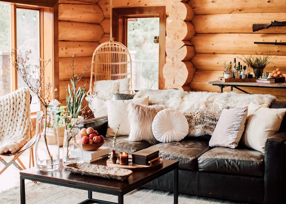 Just a few steps away, a cozy oversize leather couch, a collection of textured throw pillows, and a wood-topped coffee table with industrial details contribute to the overall mountain vibe of the space, explains Kula.