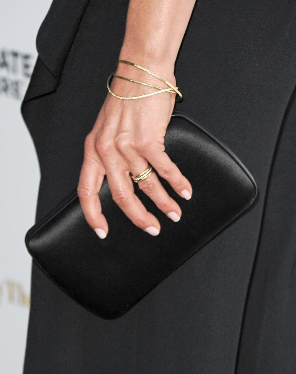 <p>After tying the knot, Aniston transitioned to a much more classic dual gold band, with small diamonds sandwiched between. <em>[Photo: Getty]</em> </p>