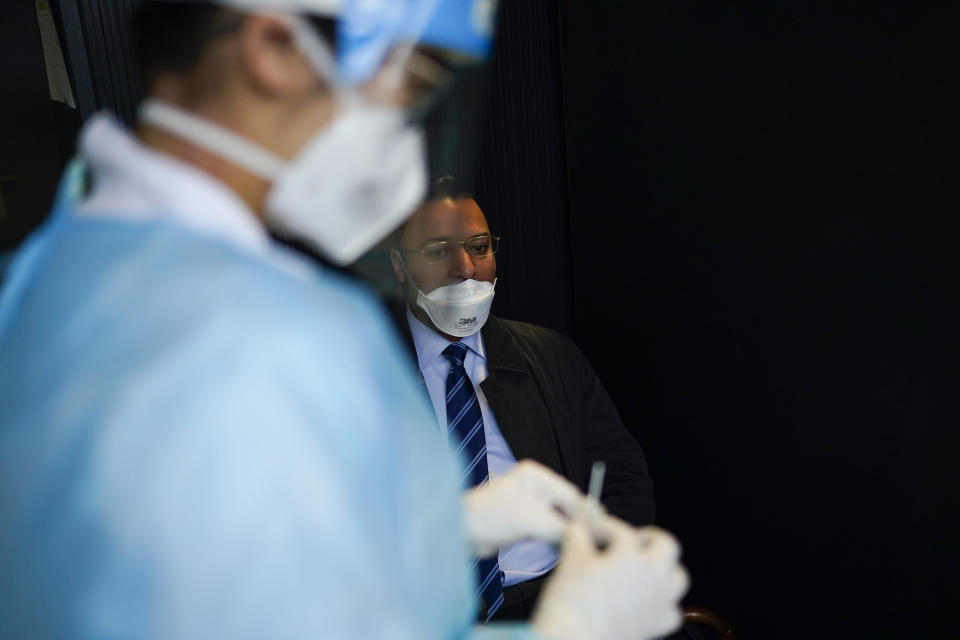 A medical worker, wearing a full protective gear, takes a nose swab from a traveller who arrived from U.K., to be tested for COVID-19 in a Red Cross test center at Gare du Midi international train station in Brussels, Tuesday, Jan. 19, 2021. Belgium is strengthening its rules for travellers entering the country by train or bus in a bid to limit the spread of a more contagious variant of the coronavirus detected in Britain. (AP Photo/Francisco Seco)