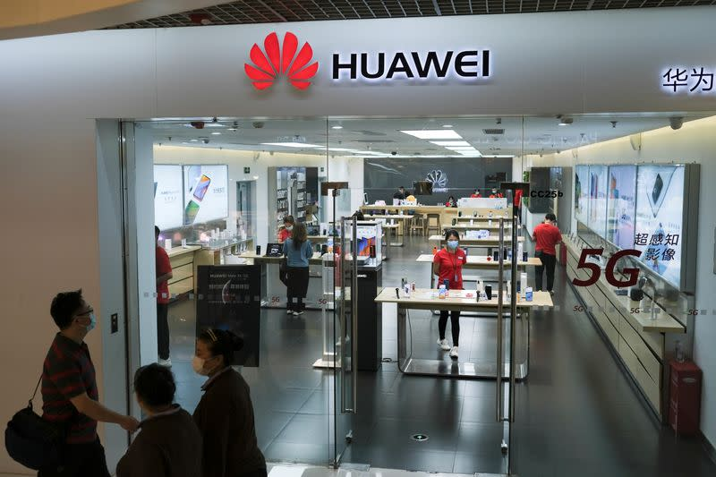 People wearing face masks walk past a Huawei store at a shopping mall, following an outbreak of the coronavirus disease (COVID-19), in Beijing