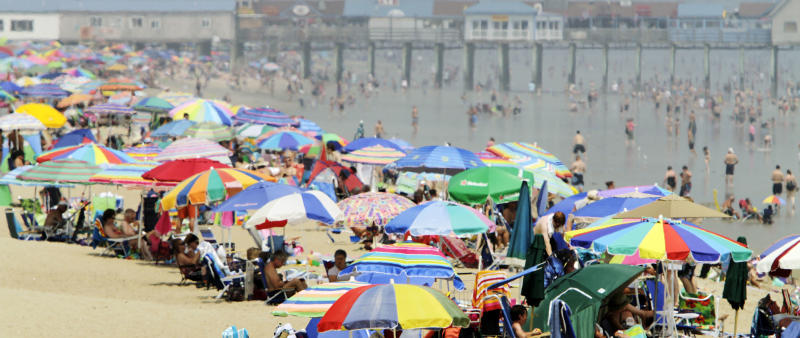 FILE - This July 12, 2011 file photo shows beach umbrellas with beach enthusiasts crowding the shores of Old Orchard Beach, Maine. The miles of white-sand beach in the oceanfront town of Old Orchard Beach will dispel any notion that Maine's coastline is all rough and rocky. The beach is a 20-minute drive from Portland and stretches for seven miles from Scarborough to Saco. When you're not on the beach itself, the town has carnival rides and amusements, gifts shops and plenty of restaurants and takeout spots with food like pizza, fried dough and cotton candy. (AP Photo/Pat Wellenbach, file)