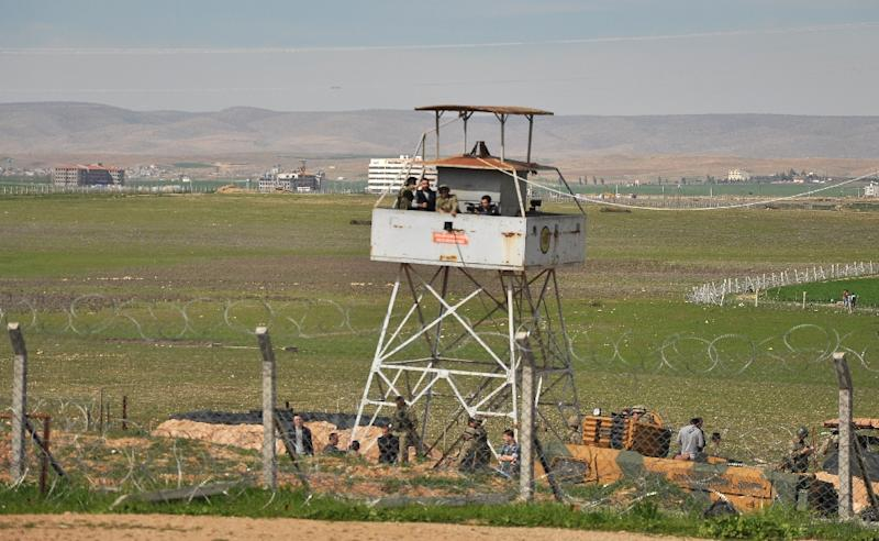 Turkish soldiers keep watch from an observation tower on the border with Syria's Hasakeh province on March 7, 2015