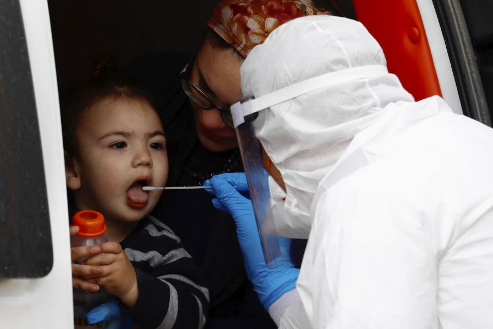 An ultra-Orthodox Jewish boy receives a COVID-19 test by a medical personnel wearing protective gear as part of the government's measures to stop the spread of the coronavirus in the orthodox city of Bnei Brak, a Tel Aviv suburb, Israel, Tuesday, March 31, 2020. (AP Photo/Ariel Schalit)