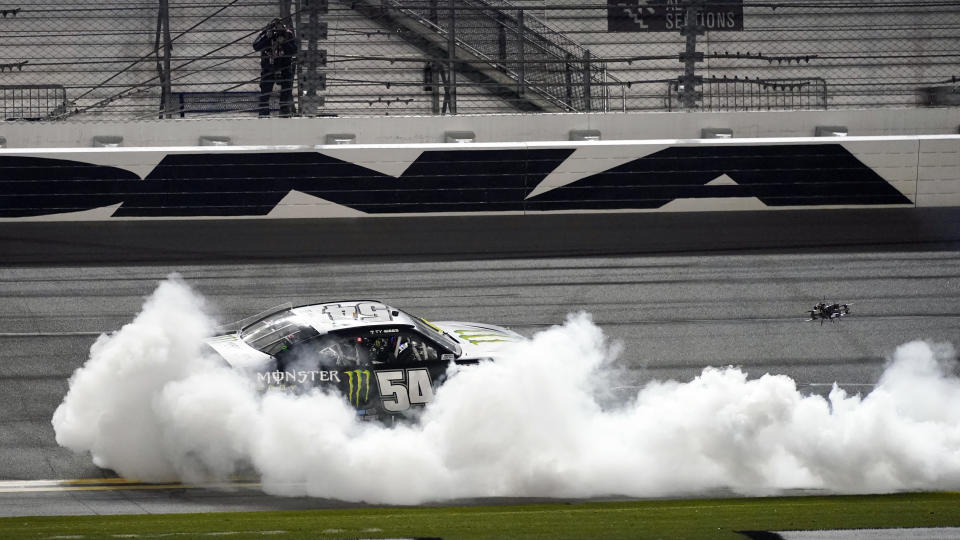 Ty Gibbs (54) celebrates with a burnout in front of the grandstands after winning the NASCAR Xfinity Series road course auto race at Daytona International Speedway, Saturday, Feb. 20, 2021, in Daytona Beach, Fla. (AP Photo/John Raoux)