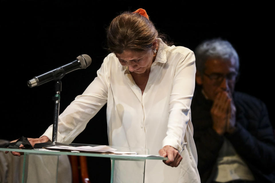 Former Colombian presidential candidate Ingrid Betancourt, who was abducted while campaigning by the Revolutionary Armed Forces of Colombia, FARC, rebels, cries as she stands on the rostrum during an event at the Truth Commission to commemorate victims of the country's decades-long armed conflict, in Bogota, Colombia, Wednesday, June 23, 2021. (AP Photo/Ivan Valencia)
